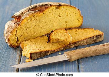 corn bread with knife on blue wooden background