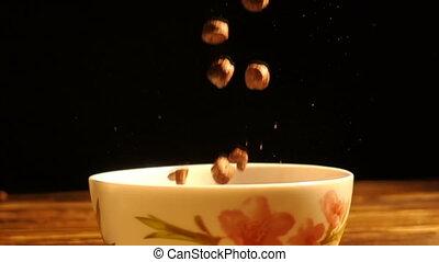 corn breakfast cereals falling in a bowl, slow motion.
