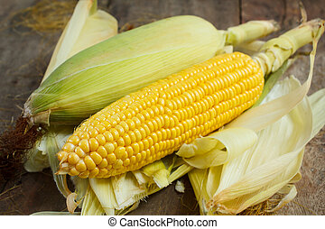Corn cobs on wood background, still life. - Corn cobs on ...