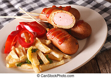 Corn dog, french fries and vegetables on a plate close-up. horizontal