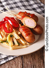 Corn dog, french fries and vegetables on a plate close-up. Vertical