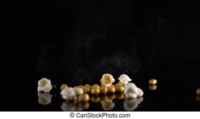 corn exploding on a black surface, slow motion