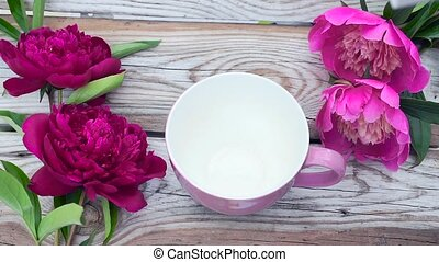 Corn flakes are poured into a pink Cup. The video is slowed down 2 times. Old wooden Board with peony flowers. Healthy Breakfast.