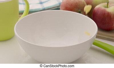 Corn flakes falling in white bowl
