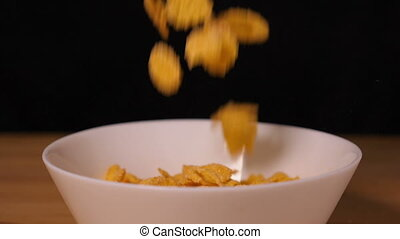 Corn flakes falling into a plate