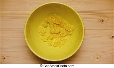 Corn flakes in a yellow bowl with milk. Stop motion, animation