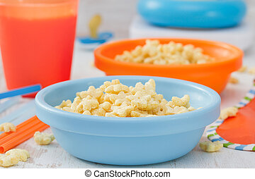 corn flakes in blue bowl on white wooden background