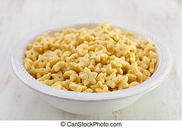 corn flakes in bowl on white wooden background