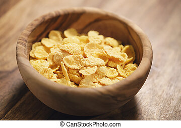 corn flakes in wood bowl closeup