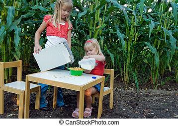 Little girls having breakfast in a cornfield.
