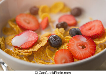 corn flakes with berries in white bowl for breakfast on table