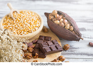 Corn kernels in wooden plates and popcorn with Caramel and chocolate cream on wooden table.