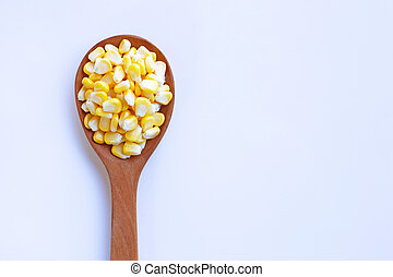 Corn seeds on wooden spoon, white background
