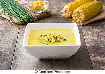 Corn soup in white bowl on wooden background