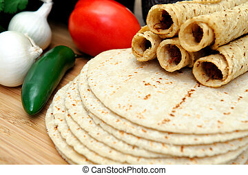 Taquitos with other natural ingredients including homemade tortillas, avocados, tomatoes, small sweet onions and jalapeno chilies