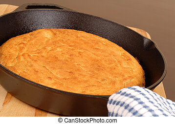 Cornbread made in a cast iron skillet resting on a cutting ...