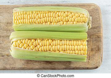 Corncob - Fresh raw corncob on a chopping board