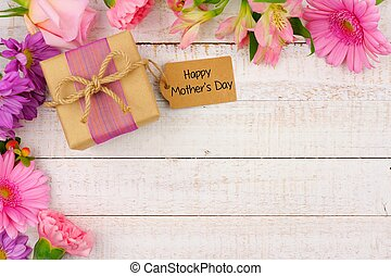 Corner border of flowers with Mothers Day gift and tag against white wood