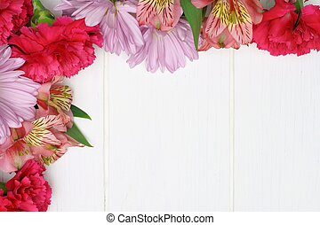 Corner border of pink carnation, daisy and lily flowers against white wood
