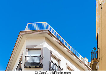 Corner of apartment building under blue sky