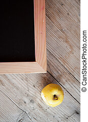 corner of blank school chalkboard with a yellow apple near her