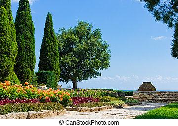 Corner of botanic garden with flowers and sea