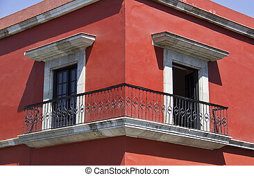 corner of red house with windows and balcony