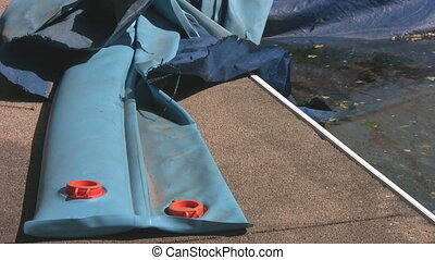 Corner of winterized pool with water bags - The corner of a...
