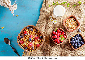 Cornflakes and other cereals with fresh fruits of raspberries, blueberries and milk on healthy breakfast. Above view.