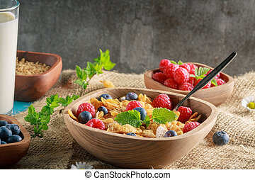 Cornflakes and other cereals with fresh fruits of raspberries, blueberries and milk on healthy breakfast.