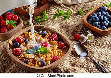 Cornflakes and other cereals with fresh fruits of raspberries, blueberries and pouring milk on healthy breakfast.