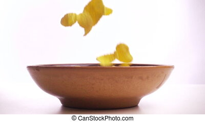 cornflakes falling in the bowl on white background, slow motion