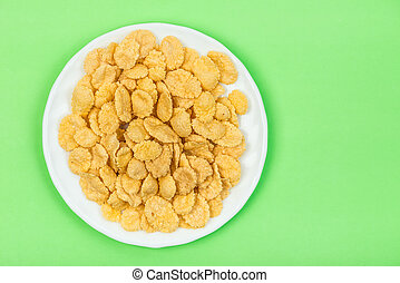 Cornflakes isolated close up on green