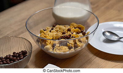 Cornflakes with chocolate balls and milk in a glass bowl on a wooden table with a jug of milk and a plate with a spoon on it. Healthy food concept. Quick breakfast concept