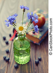 Cornflowers in vintage bottle with berries on wooden...