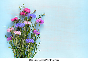 Cornflowers on blue wooden background