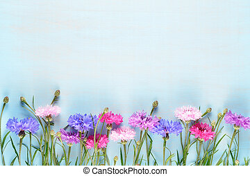 Cornflowers on blue wooden background with copy-space