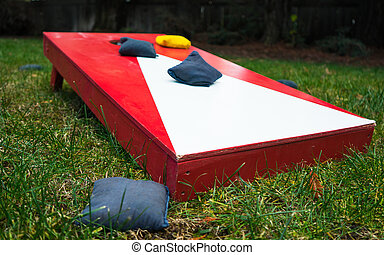 Close-up of cornhole toss game board with bean bags.
