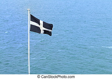 Cornish independence flag flying over the blue ocean