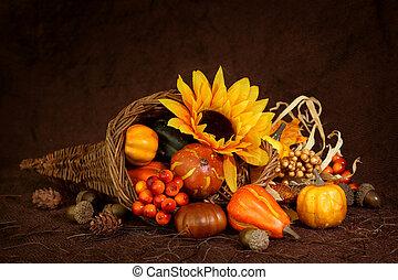 Cornucopia with pumpkins on brown background
