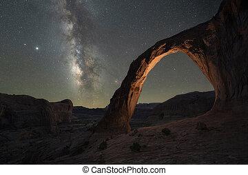 Corona Arch lit at night under the Milky Way Galaxy