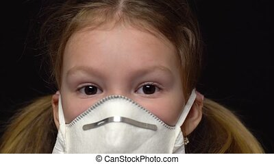 Coronavirus and Air pollution concept. Little girl wearing mask for protect. Wuhan coronavirus and epidemic virus symptoms. Stares at the camera. Encourages a sense of guilt in front of children. Isolated on a black background
