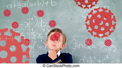 Animation of Covid 19 coronavirus cells spreading over thinking schoolboy in class with chalkboard in the background. Education back to school coronavirus pandemic concept digitally generated image.