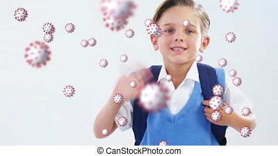 Animation of Covid 19 coronavirus cells spreading over happy schoolboy waving with backpack on white background. Education back to school coronavirus pandemic concept digitally generated image.