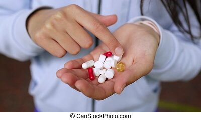 Coronavirus. Covid-19. A man or woman takes and shows pills.