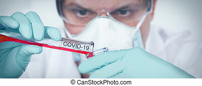 Coronavirus covid 19 infected blood sample in sample tube in hand of scientist with biohazard protection clothing in corona virus covid 19 research laboratory, coronavirus covid 19 vaccine research concept