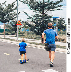 Coronavirus COVID 19 Sport active outdoor family life. Back view Father running son riding scooter movement, sidewalk background, having workout enjoying together. Concept run from problems
