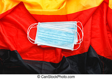 Coronavirus in Germany. Protective surgical face mask on Deutsch national flag. Germany quarantine, protection coronavirus symbol of doctor, nurse, medical worker. Medicine health care. Covid-19