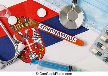 Coronavirus, nCoV concept. Top view protective breathing mask, stethoscope, syringe, tablets on the flag of Serbia.