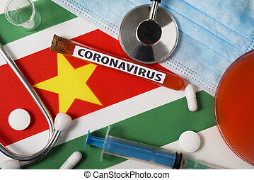 Coronavirus, nCoV concept. Top view protective breathing mask, stethoscope, syringe, tablets on the flag of Suriname.